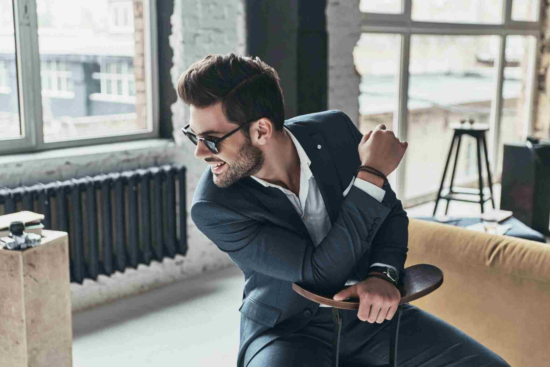 Men's clothing on display by a male model in black shades and playful mood