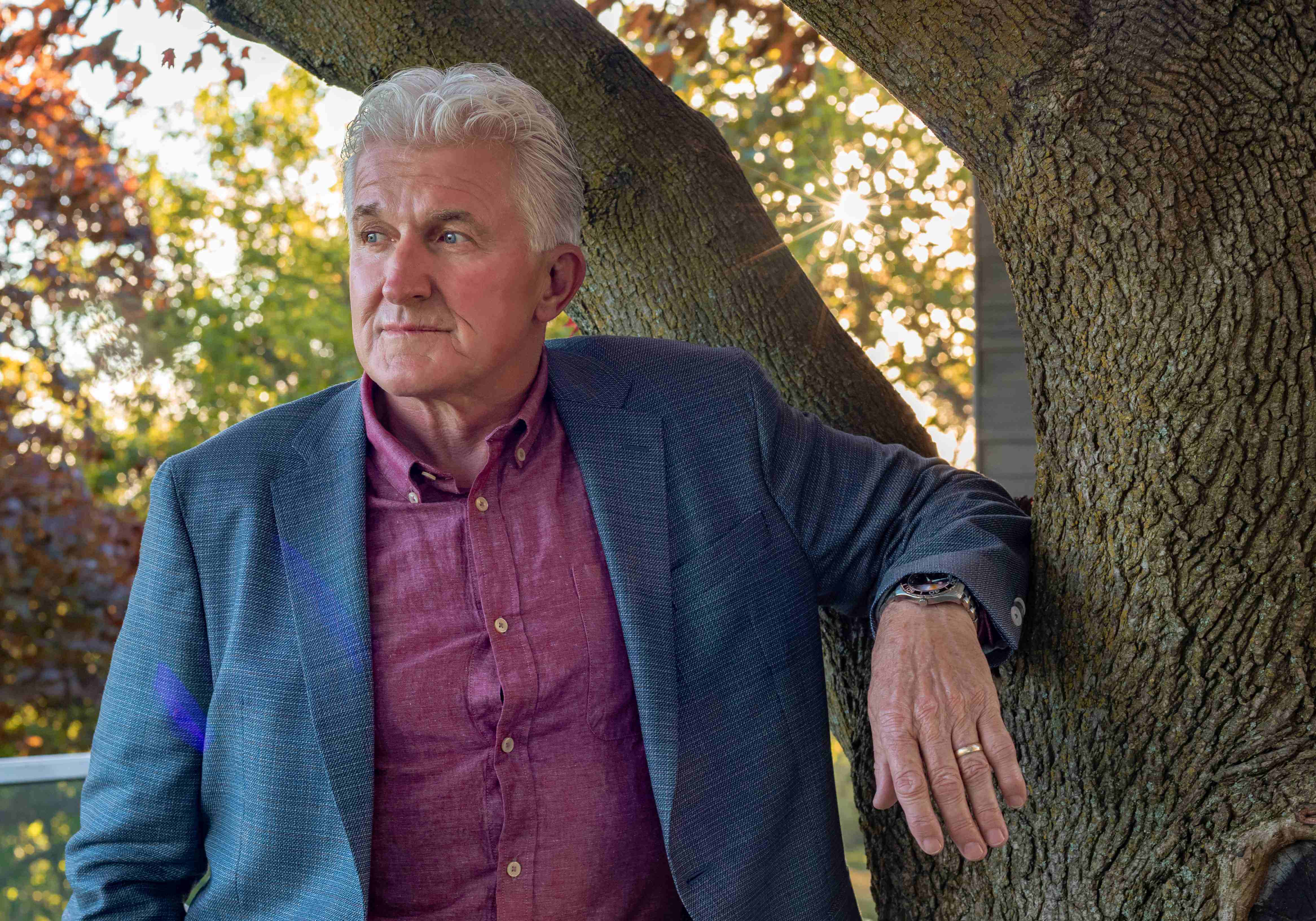 A graceful, smart, fashionable mature man in casual suit standing in front of a tree - photo on the website of Richard's Clothing - a men's clothing store London, Ontario